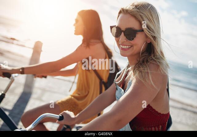 Lächelnde junge Frau Reiten Fahrrad mit ihrer Freundin an einem sonnigen Tag. Zwei Freundinnen, Radfahren auf Stockbild