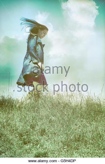 Windige Frau im schwarzen Mantel Stockbild