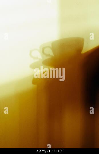 Shadow Detail einer Teetasse und Untertasse, in goldenen Nachmittag Sonnenlicht eingefangen. Stockbild