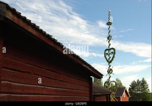 Mittsommer-Pol in schwedischen Dorf mit traditionell Häuser in rot lackiert. Stockbild