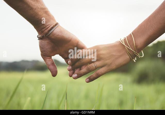 Horizontalen Schuss junges Paar zu Fuß durch Wiese Hand in Hand mit Fokus auf Händen. Stockbild