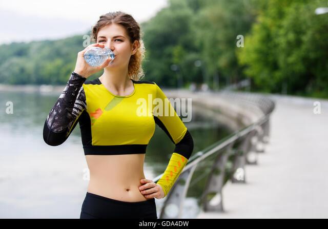 Kaukasische Mädchen ist Trinkwasser nach dem Joggen Stockbild