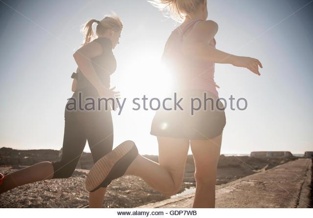 Zwei junge Damen, die entlang der sonnigen Küste, Seapoint, Kapstadt, Südafrika Stockbild