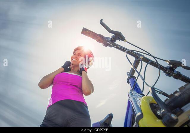 Frau mit Mountainbike setzen ihren Helm auf, Kanton Wallis, Schweiz Stockbild