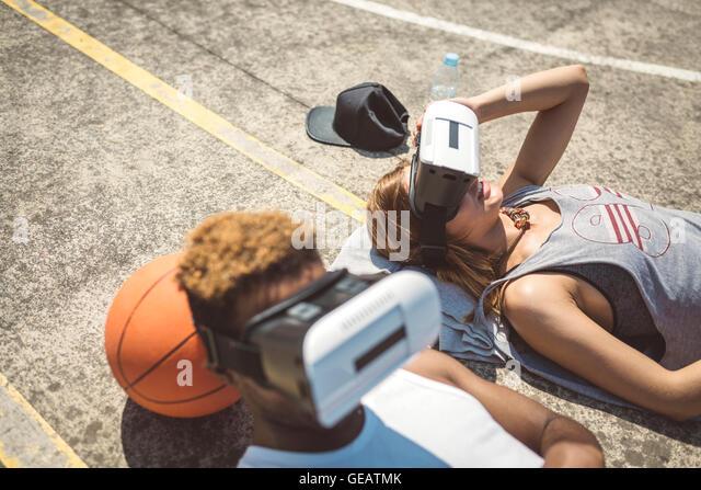 Junges Paar mit virtual-Reality-Brille, Köpfe auf Basketball ruht Stockbild