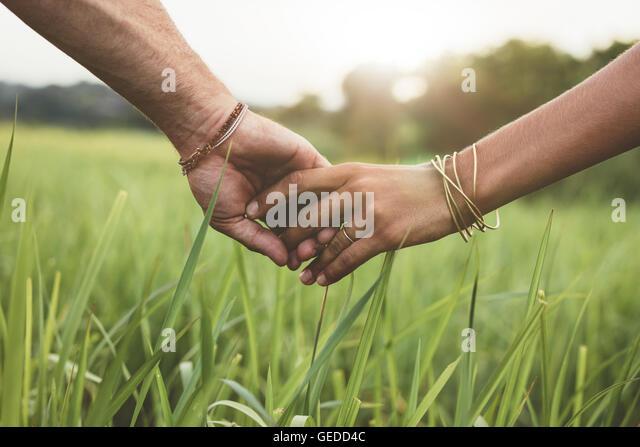 Schuss von romantisch zu zweit Hand in Hand in ein Feld. Schuss von Mann und Frau mit der Hand in der hand zu Fuß Stockbild