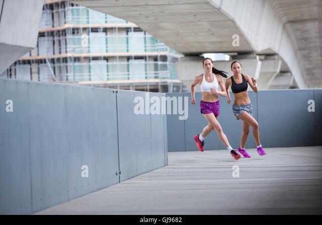 -MODELL VERÖFFENTLICHT. Zwei junge Frauen Rennen. Stockbild
