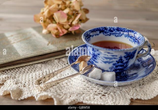 Nostalgische Szene Tee in antike China-blauen und weißen Tasse und Untertasse mit braunen und weißen Zuckerwürfel Stockbild