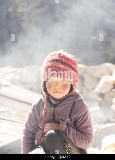 Nepalesisches Mädchen sitzt im kalten Winter in der Nähe von Namche Stockbild