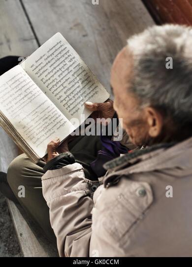 Ein älterer Mann liest aus ein Gebetbuch in der Boudhanath-Pagode in Kathmandu Nepal. Stockbild