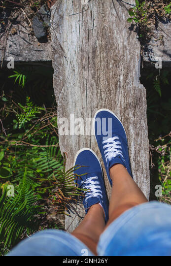 Nahaufnahme von Frau balancieren auf Holzbrett auf Brücke Stockbild