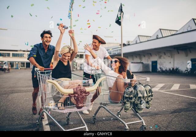 Junge Freunde, die Spaß am Einkaufswagen. Multiethnische Jugendlichen racing auf Warenkorb. Stockbild