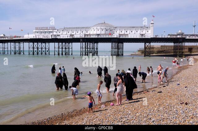 Mix der Kulturen auf Brighton Beach mit muslimischen Frauen und Familien unter den Massen genießen eine Paddel Stockbild