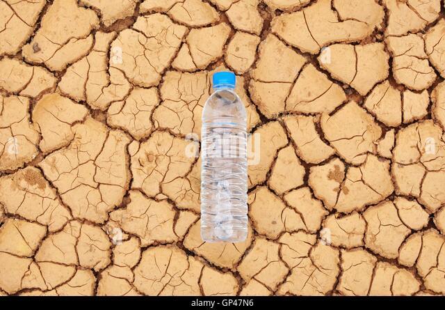 Trinkwasser-Flasche auf trockenen Untergrund Stockbild