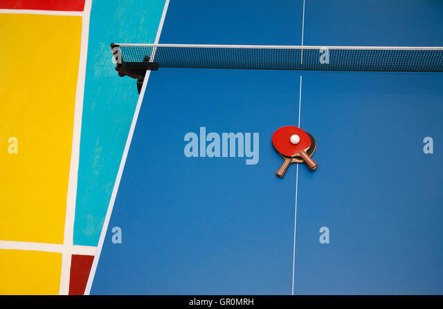 Tischtennisschläger blau rot und schwarz und eine Kugel auf eine Tischtennisplatte, Ansicht von oben Stockbild