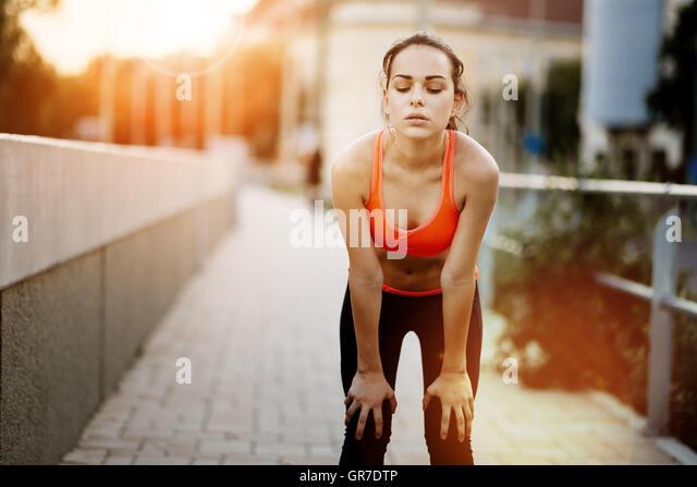 Müde weibliche Jogger, ruhen Sie sich nach Beendigung ausgeführt Stockbild