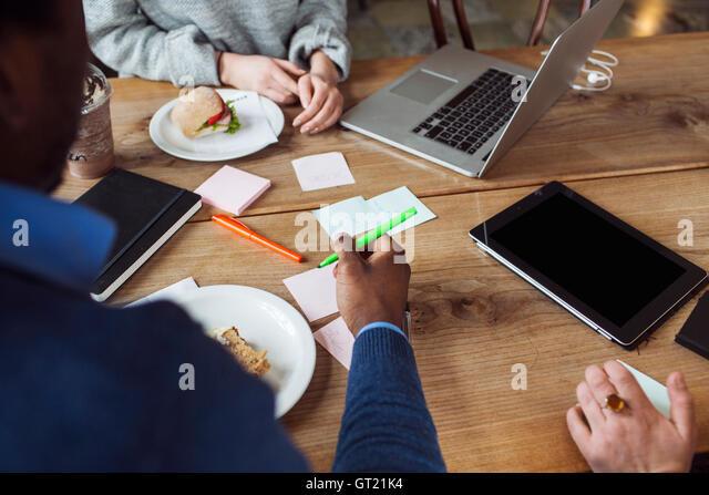 Zugeschnittenes Bild Freunde arbeiten beim Sandwich bei café Stockbild