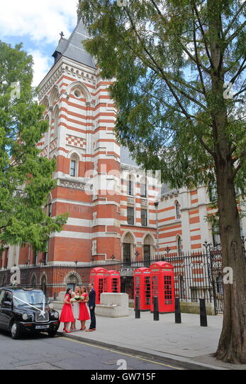 Ein Mann und drei junge Frauen posieren vor einer Trauung auf Carey Street, London, Großbritannien Stockbild