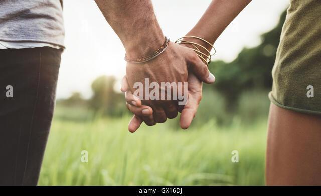Junges Paar hand in hand durch die Wiese gehen. Schuss mit Fokus auf Händen von Mann und Frau hautnah. Stockbild