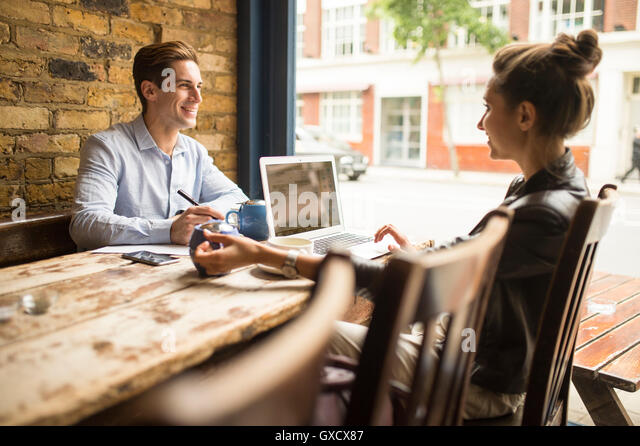 Geschäftsmann und Frau arbeitet im Café, London, UK Stockbild