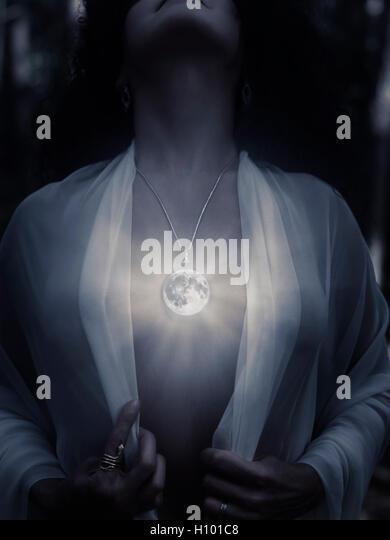 Junge Frau trägt einen magischen Vollmond Anhänger Leuchten auf der nackten Brust bei Nacht, künstlerische Stockbild