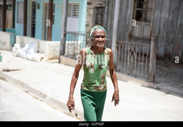 Eine ältere kubanische Frau, gekleidet in grüne Kleidung ist Fuß auf der Straße in Santiago Stockbild