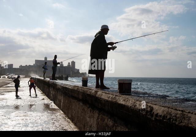 Eine Gruppe von kubanischen Fischer Silhouette auf dem Deich am Malecón in Havanna Kuba Stockbild