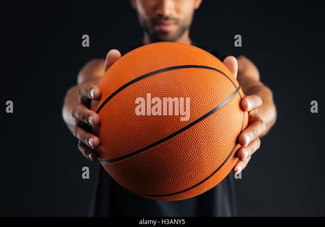 Zugeschnittenes Bild eine fokussierte junge afrikanische Basketballspieler geben Ball auf schwarzem Hintergrund Stockbild
