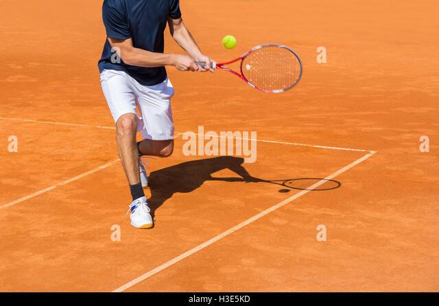 Tennisspieler in Aktion auf dem Sandplatz an einem sonnigen Tag Stockbild