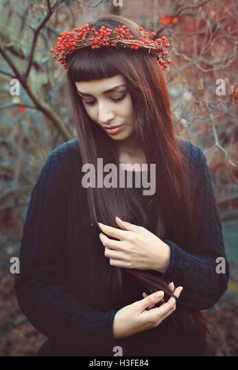 Herbst-Porträt einer schönen Frau mit langen Haaren und Beeren Krone Stockbild
