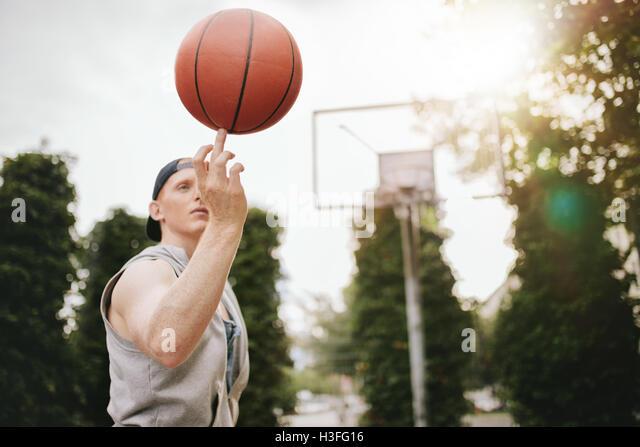 Junger Mann Ausgleich Basketball an seinem Finger auf Freiplatz. Streetball Spieler den Ball drehen. Basketball Stockbild