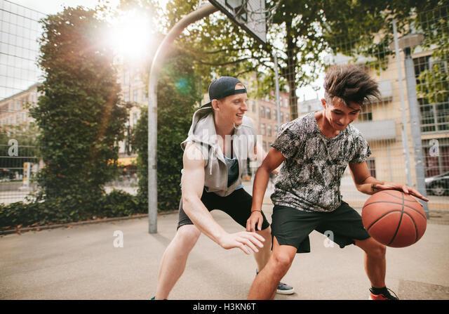 Zwei junge Freunde, Basketball auf Platz im Freien zu spielen und Spaß haben. Streetball Spieler mit einem Stockbild