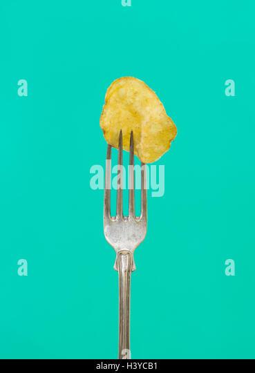 Eine Kartoffel-Chips auf der Gabel. Nahaufnahme von salzig und Fett Snack. Konzept der ungesunde Ernährung. Stockbild