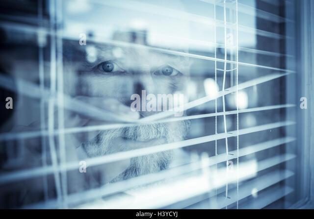 Blick aus Fenster durch Vorhänge Greis. Konzept der Beobachtung und Überwachung der Nachbarschaft. Fühlen Stockbild