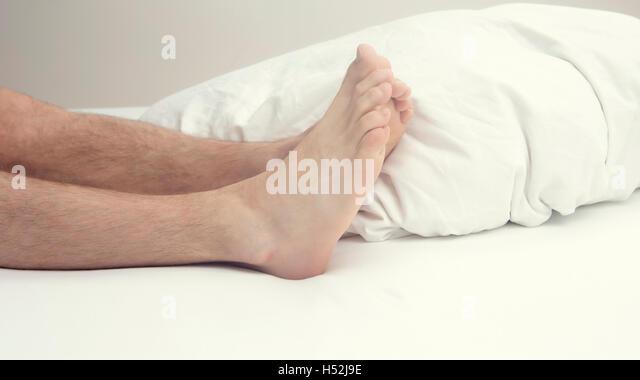 Nahaufnahme von haarige Beine und Füße der Mann im Bett in weiße Bettwäsche Stockbild