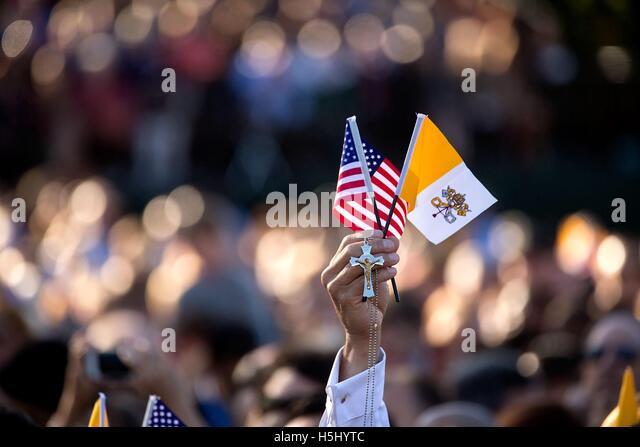 Ein Gast hält die amerikanische Flagge, die Flagge der Vatikanstadt und ein Kreuz bei Ankunft Staatsakt für Stockbild