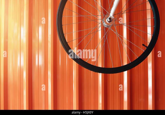 Fahrrad-Rad hängen an der Garagenwand Orange Stockbild
