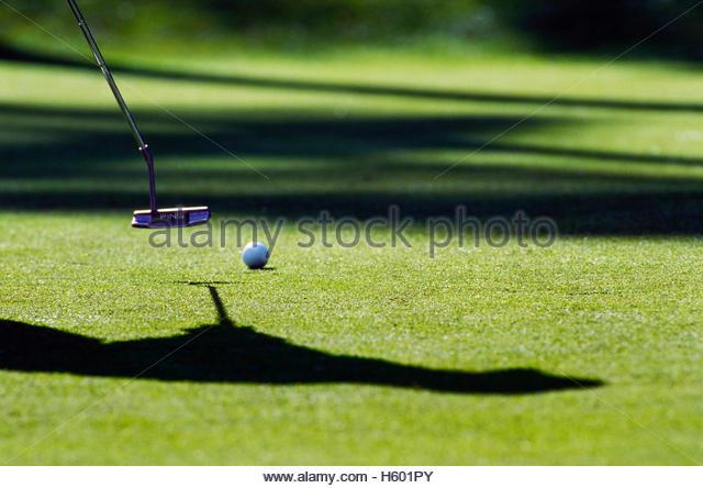Golfer zwischen Schatten setzen. Stockbild