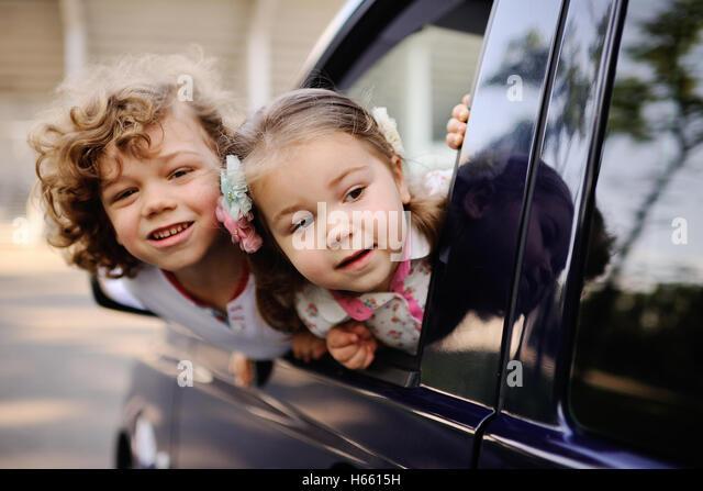 Kinder schauen aus einem Autofenster Stockbild