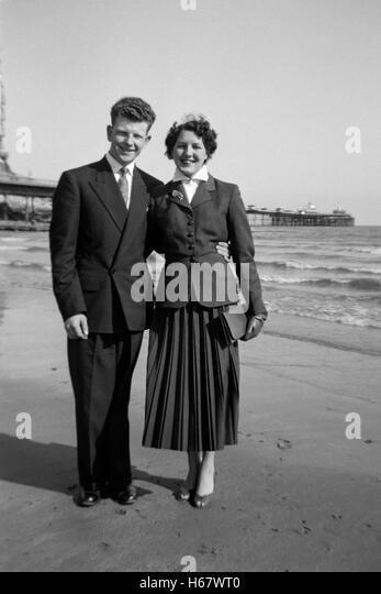 junges Paar im Urlaub an der Küste England der 1950er Jahre Stockbild