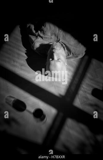 Alter Mann auf Boden ruhen. Schwarz-weiß-Porträt mit tiefen Schatten. Konzeptbild von Einsamkeit und Ruhestand. Stockbild