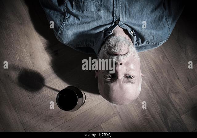 Alter Mann mit Weinglas auf der Seite auf Boden ruhen. Konzeptbild von Einsamkeit und Ruhestand. Stockbild