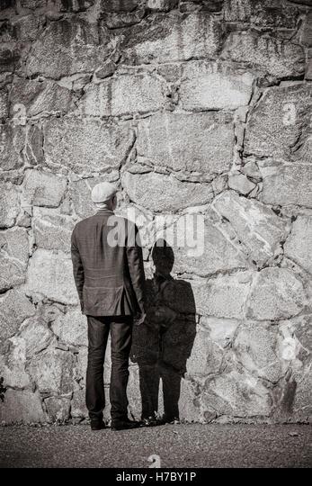 Alter Mann stand vor der Steinmauer. Sonnenschein und schweren Schatten. Gebäudehülle mit Textfreiraum. Stockbild