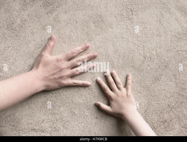Zwei Hände verbinden. Erwachsener und Kind hand treffen, eine Wand zu berühren. Konzeptbild Verbindung Stockbild