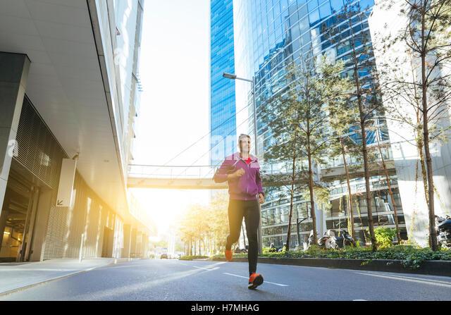 Athlet mit Kopfhörern laufen in der Stadt Stockbild