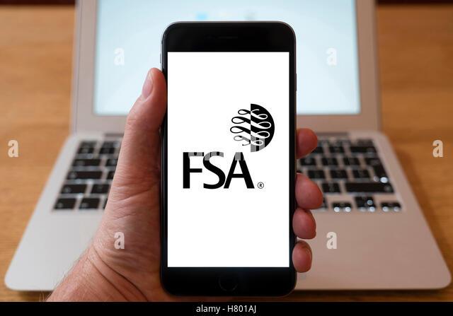 Mit iPhone Smartphone zum Logo der Financial Services Authority FSA anzeigen Stockbild