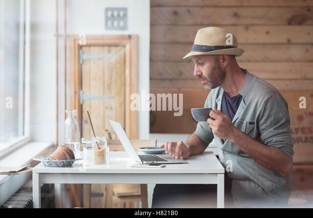 Mitte der 30er Jahre Mann arbeitet am Laptop im Café Stockbild