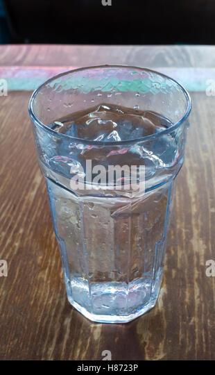 Ein Kunststoff-Glas mit eiskaltem Wasser auf einem alten Holztisch H2O Stockbild