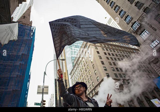 """New York, USA. 12. November 2016. Ein Mann """"Wellenlinien"""" einen schwarzen US-Flagge in der Nähe von Stockbild"""
