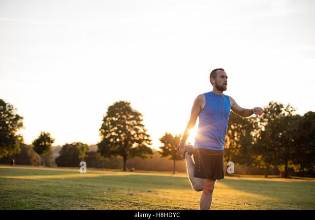 Junger sportlicher Mann stretching nach einem Lauf im park Stockbild
